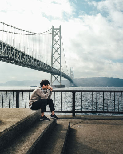 Love Camera Real People Sky Water Architecture Full Length Built Structure Lifestyles Connection Cloud - Sky One Person Leisure Activity Railing Bridge Nature Casual Clothing Sitting Bridge - Man Made Structure Men Outdoors It's About The Journey 2018 In One Photograph