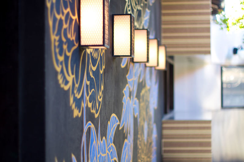 Close-Up Of Lit Wall Lamps In A Row