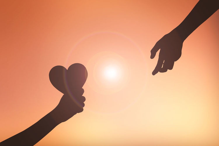 Cropped Image Of Silhouette Hands With Heart Shape Against Orange Sky