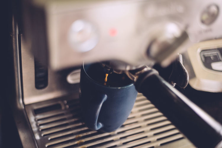 Close-up of fresh coffee pouring out of machine