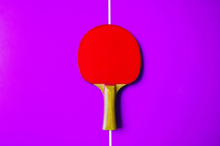 Directly above shot of red table tennis racket on purple table