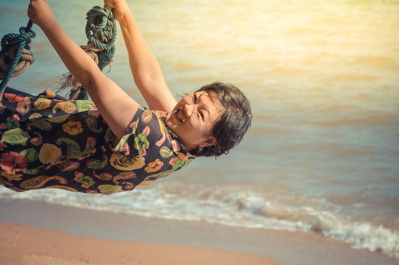 Mature woman swinging against sea at beach
