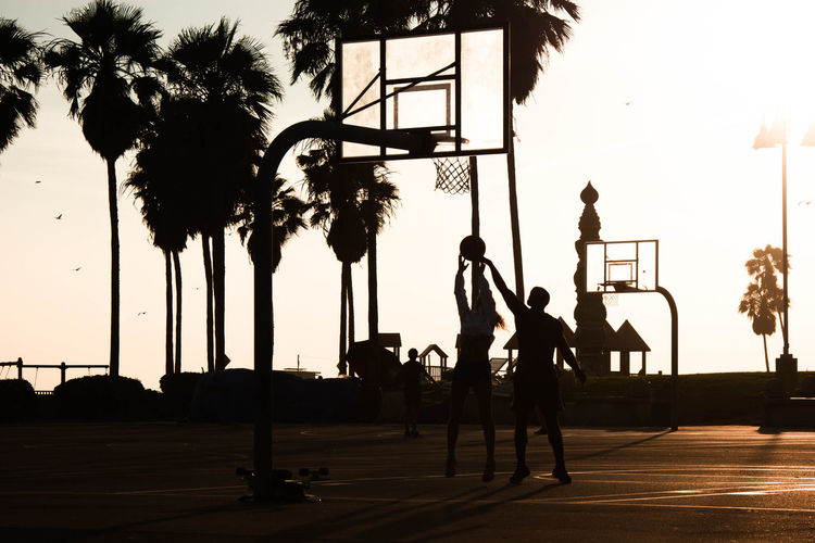 Silhouette friends playing basketball against sky during sunset