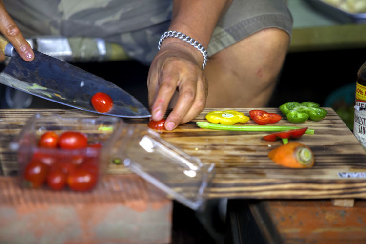 Barbeque Bell Pepper Celery Chef Close-up Cooking Cool Cropped Cutting Cutting Board Day Delicious Focus On Foreground Food Freshness Knife Leisure Activity Lifestyles Outdoors Part Of Selective Focus Tomato Unrecognizable Person Wood - Material Wooden