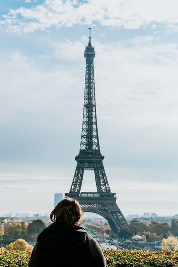 Rear view of woman standing by eiffel tower