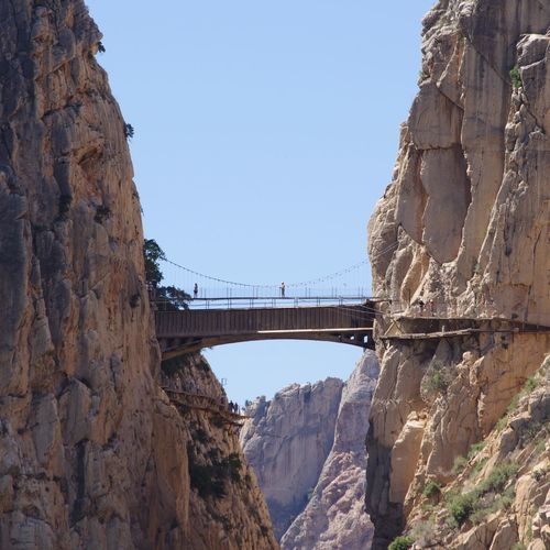 Bridge Amidst Rocky Mountains Against Clear Sky At Caminito Del Rey