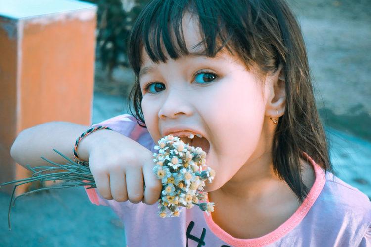 Portrait of girl eating flower outdoors