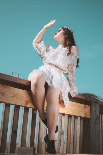 Low angle view of woman sitting on seat against sky