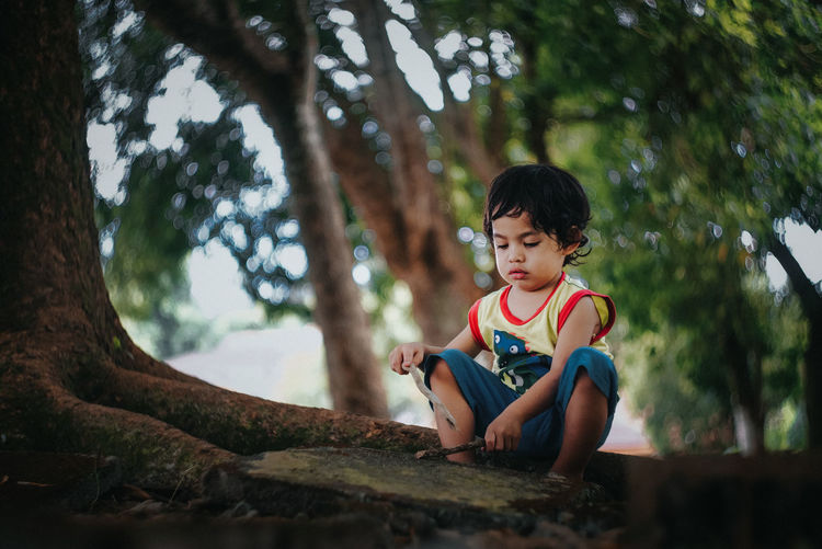 Cute boy sitting on tree roots in park