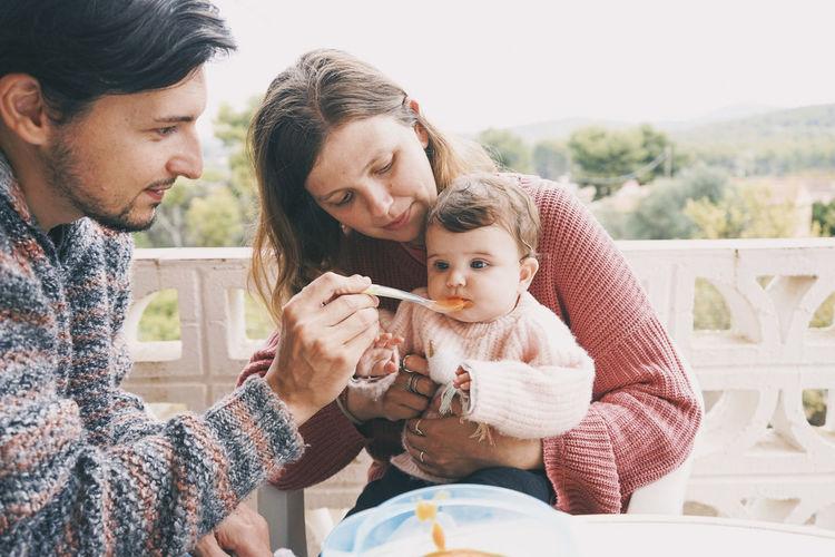 Man and woman feeding baby girl in balcony