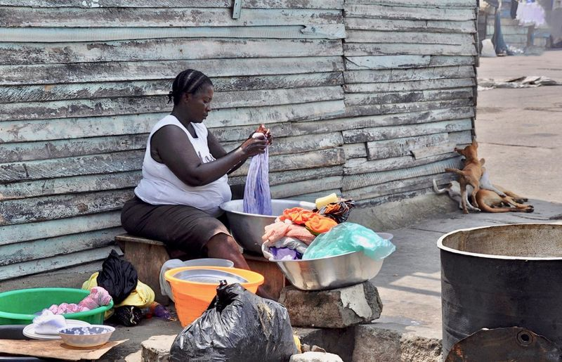 Mature woman washing clothes while sitting outdoors