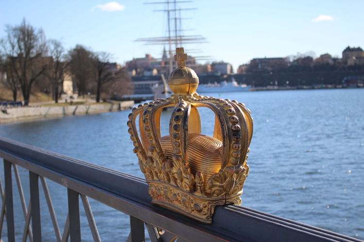 Artificial crown on railing by river during sunny day