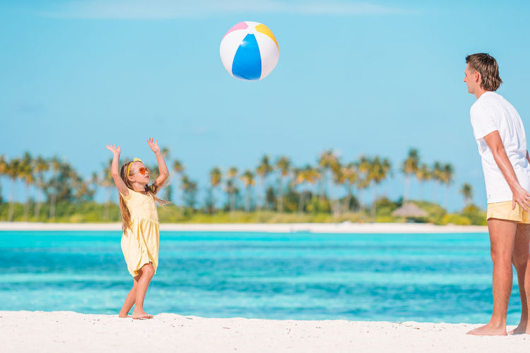 Full length of father and daughter playing with ball at beach