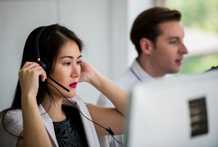 Female customer representative talking over headset in office