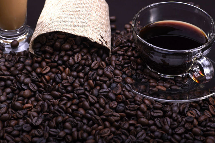 A cup of coffee with coffee beans over the black background Food And Drink Coffee Roasted Coffee Bean Drink Refreshment Coffee - Drink Food Freshness Indoors  Brown Caffeine No People Close-up Still Life Abundance Mug Cup Coffee Bean Roasted Large Group Of Objects Crockery