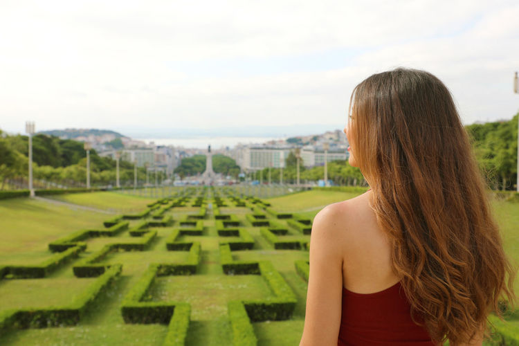 Rear View Of Woman Standing At Ornamental Garden Against Cloudy Sky