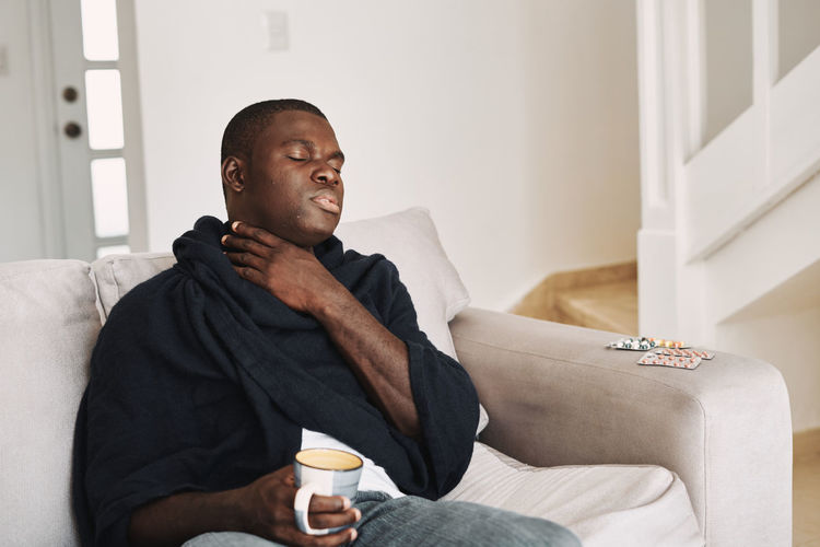 Mid adult man with coffee cup sitting on sofa