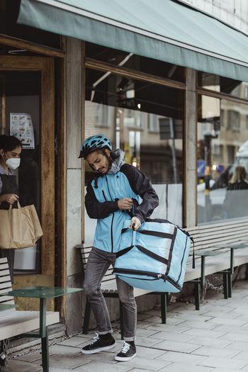 Full length of woman standing on sidewalk in city