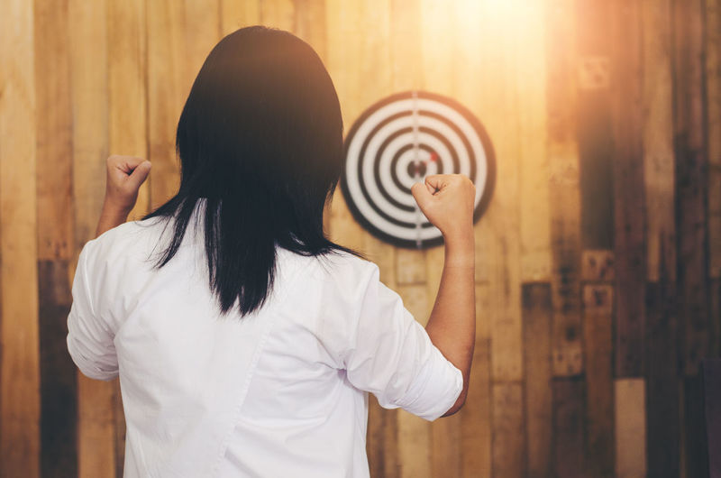 Woman Clenching Fists While Standing Against Dartboard