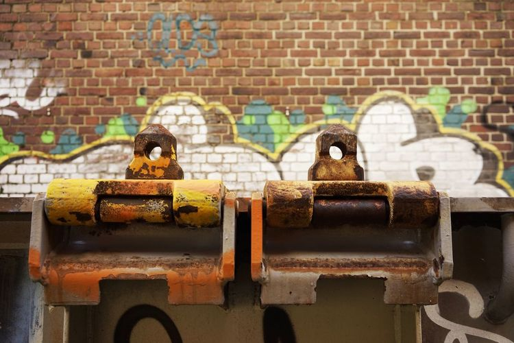 Cropped Image Of Rusty Metallic Hinges Against Graffiti On Brick Wall