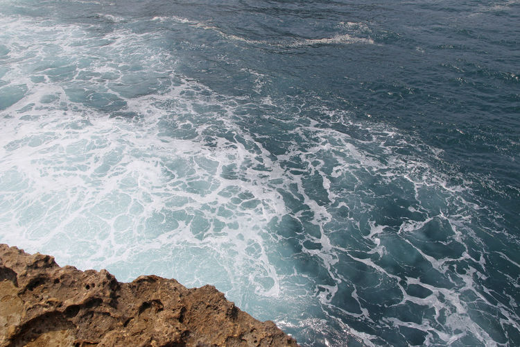 Natural rock formation with the wave at Timang Beach in sunny day, Yogyakarta, Indonesia Sunlight Sunny TimangBeach Yogyakarta Aquatic Sport Beach Beauty In Nature Day High Angle View Land Motion Nature Outdoors Rock Rock - Object Scenics - Nature Sea Solid Sport Surfing Water Wave