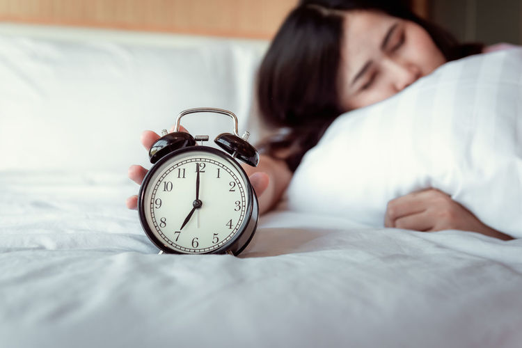 Woman with alarm clock sleeping on bed