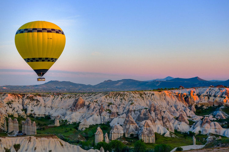 Hot air balloon over cappadocia against sky during sunset