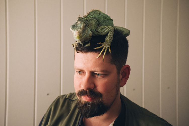 Man with iguana on head