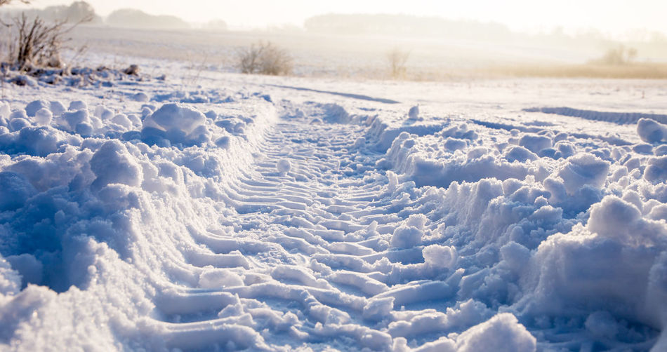 Tire tracks in the deep snow in a deserted landscape Snow Winter Cold Temperature Nature No People Tranquility White Color Day Field Tranquil Scene Environment Land Sky Frozen Landscape Plant Tire Marks Vehicle Trace Brandenburg Barnim