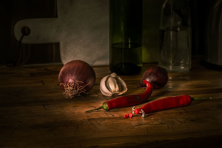 Close-up of onions with red chili and garlic on table