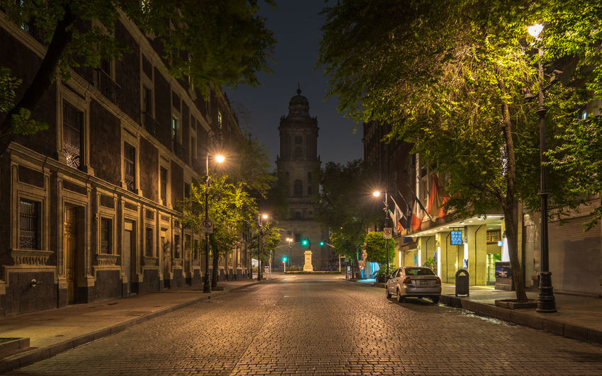 Illuminated road amidst buildings leading towards metropolitan cathedral at night