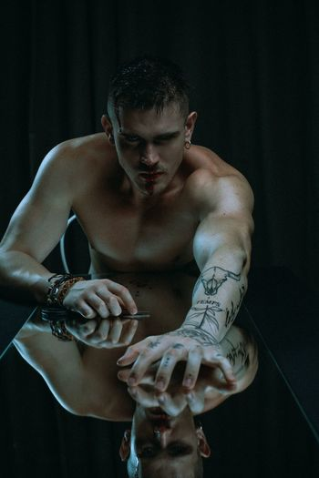 Shirtless man with tattoo sitting at table against black background
