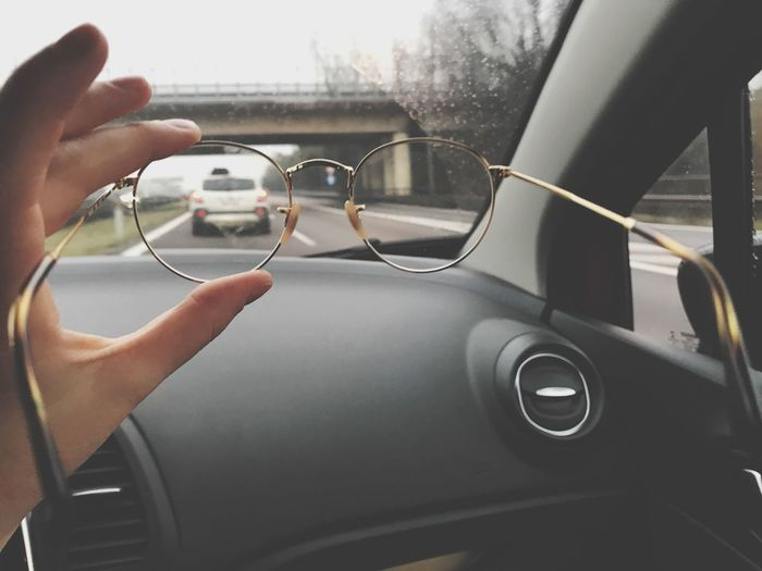 Human Hand Car Mode Of Transportation Motor Vehicle Vehicle Interior One Person Hand Glass - Material Real People Steering Wheel Land Vehicle Human Body Part Indoors  Transparent Windshield Dashboard Car Interior Transportation Travel Body Part
