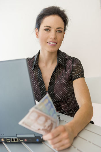 Young woman on laptop holding Euro notes 20-25 Years Old Desk Home Office Adult Business Business Person Businesswoman Computer Euro Currency Euro Notes Exchange Front View Indoors  Looking At Camera Occupation Office One Person Portrait Sitting Smiling Table Waist Up Women Young Adult