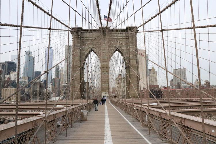 People walking on footbridge in city