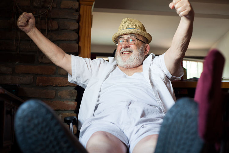 happy old man Arms Raised Beard Caucasian Chair Cheerful Comfortable Elderly Expression Front View Happiness Happy Hat Lifestyle Pensioner Relaxation Relaxing Resting Retirement Satisfaction Senior Adult Senior Men Shoes Sitting Smile White