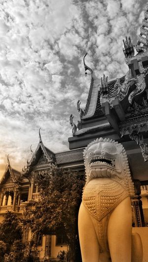 Low angle view of statue against temple building against sky