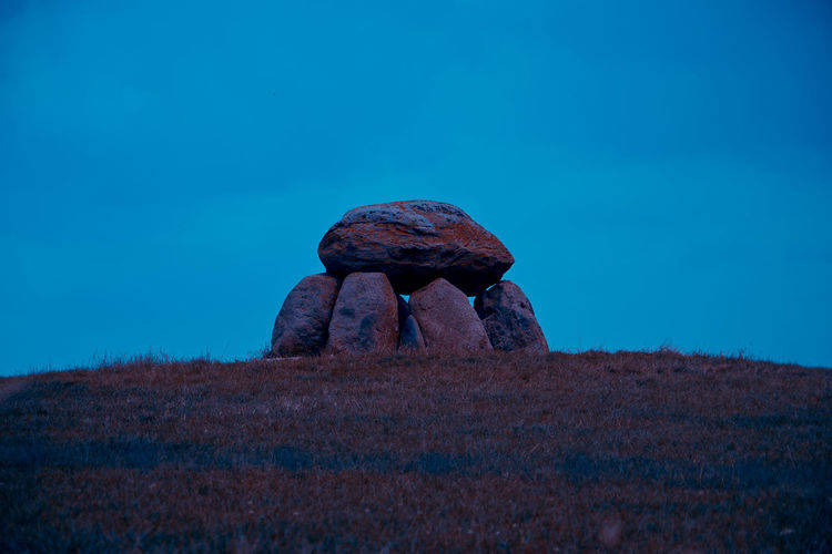 Rock on field against blue sky