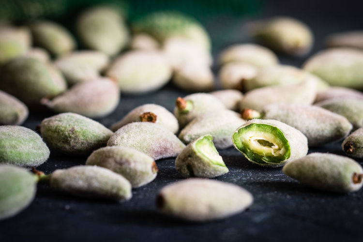 Close-up of green almonds on table
