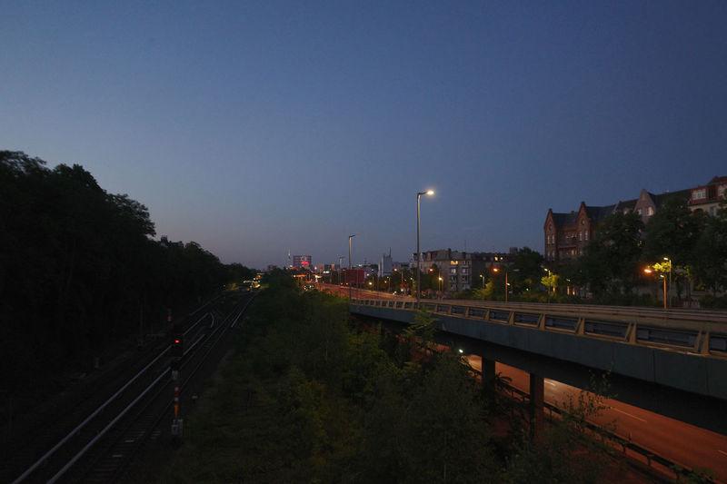 Light trails on street against sky at dusk