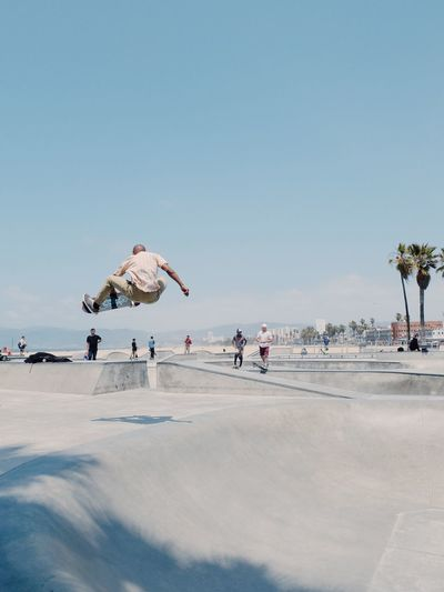 Rear View Of Man Skateboarding Against Sky