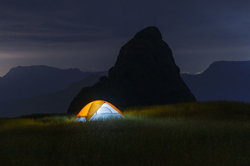 Illuminated tent on mountain against sky at night