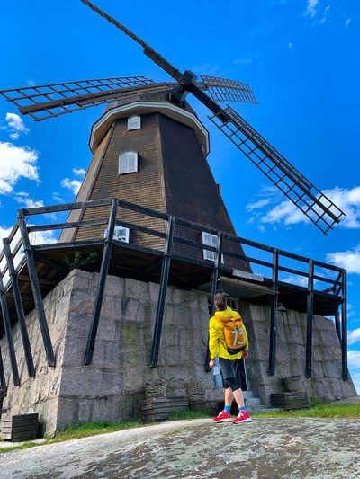 Full length of man looking at traditional windmill against sky