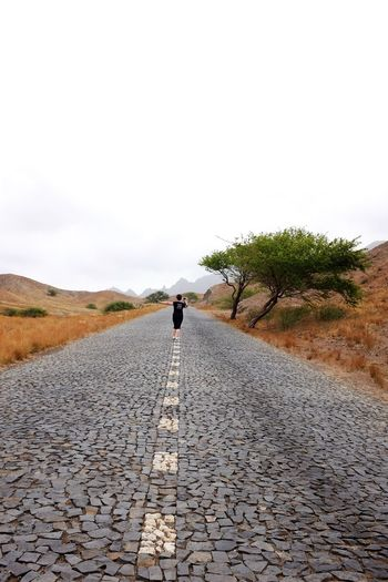 Rear View Of Woman Walking On Road Against Clear Sky
