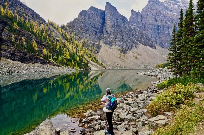 Hiker at Lake Agnes in the Canadian Rockies Mountain Scenics - Nature Beauty In Nature Leisure Activity Rock One Person Real People Lifestyles Solid Rock - Object Full Length Lake Water Mountain Range Non-urban Scene Nature Day Tranquil Scene Standing Outdoors Formation Looking At View Reflection Travel Destinations Lake Agnes