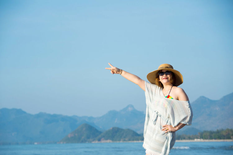 Portrait of young woman gesturing peace sign while standing at beach against clear sky