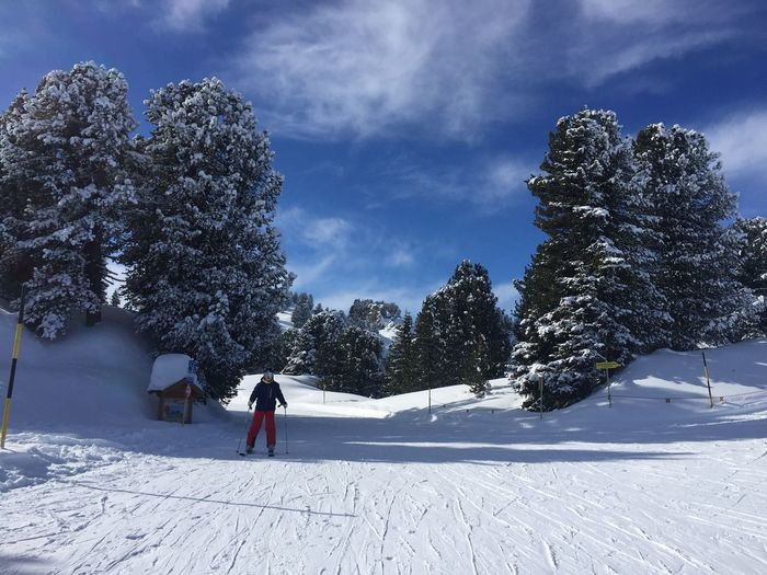 Person skiing on snowcapped landscape against sky