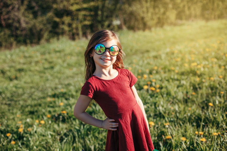Portrait of smiling girl wearing sunglasses standing on field