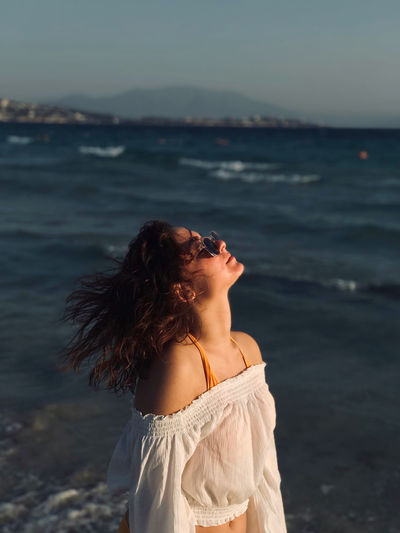 Woman with tousled hair standing at beach