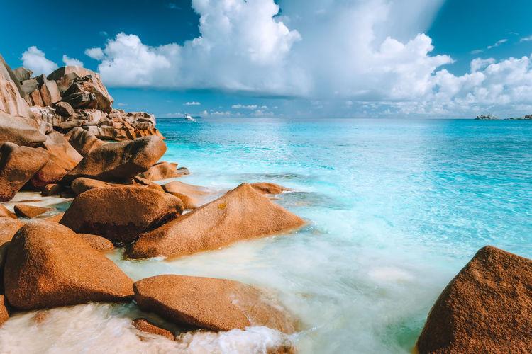 Rocks by sea against cloudy sky